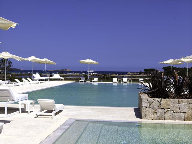 Ligbedden en parasols rondom het zwembad - Vakantie resort Paradise in Sardinie